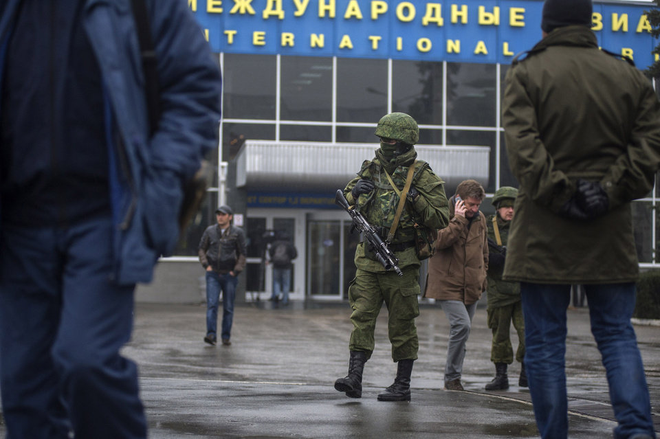 Photo - Unidentified armed man patrols a square in front of the airport in Simferopol, Ukraine, Friday, Feb. 28, 2014. Dozens of armed men in military uniforms without markings patroled the airport in the capital of Ukraine's strategic Crimea region on Friday as tensions in the country's Russian-speaking southeast escalated. (AP Photo/Andrew Lubimov)