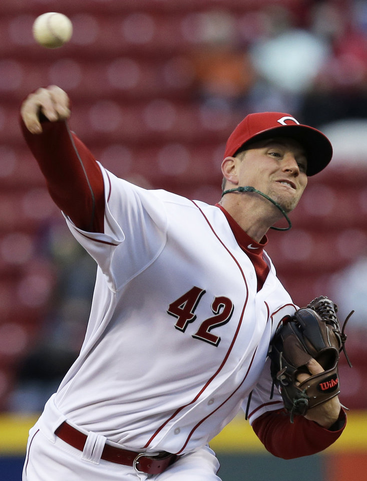 Photo - Cincinnati Reds starting pitcher Mike Leake throws to a Pittsburgh Pirates batter in the first inning of a baseball game, Tuesday, April 15, 2014, in Cincinnati. (AP Photo/Al Behrman)