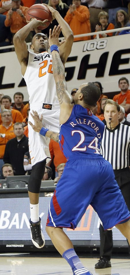 Photo - Oklahoma State 's Markel Brown (22) puts up a shot over Kansas' Travis Releford (24) during the college basketball game between the Oklahoma State University Cowboys (OSU) and the University of Kanas Jayhawks (KU) at Gallagher-Iba Arena on Wednesday, Feb. 20, 2013, in Stillwater, Okla. Photo by Chris Landsberger, The Oklahoman