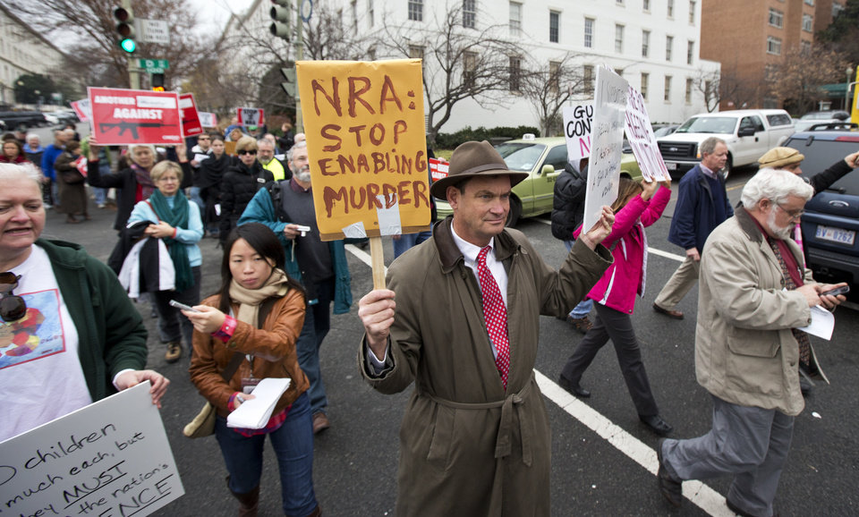 Patrick Hand, center, joins a march to the National Rifle Association headquarters on Capitol Hill in Washington Monday, Dec. 17, 2012. Curbing gun violence will be a top priority of President Barack Obama\'s second term, aides say. but exactly what he\'ll pursue and how quickly are still evolving. (AP Photo/Manuel Balce Ceneta)