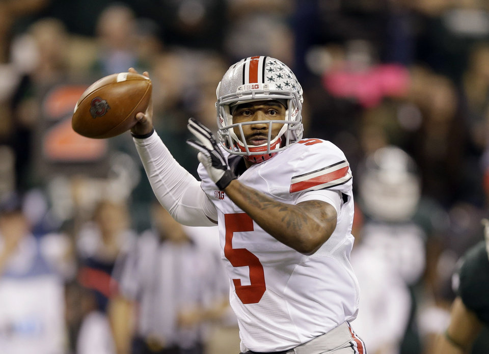 Photo - FILE - In this Dec. 7, 2013, file photo, Ohio State quarterback Braxton Miller throws a pass against Michigan State during the Big Ten Conference championship NCAA college football game in Indianapolis. Despite missing nearly three full games with a sprained knee last season, he passed for 2,094 yards and 24 touchdowns, and ran for 1,068 yards and 12 scores.  (AP Photo/Michael Conroy, File)