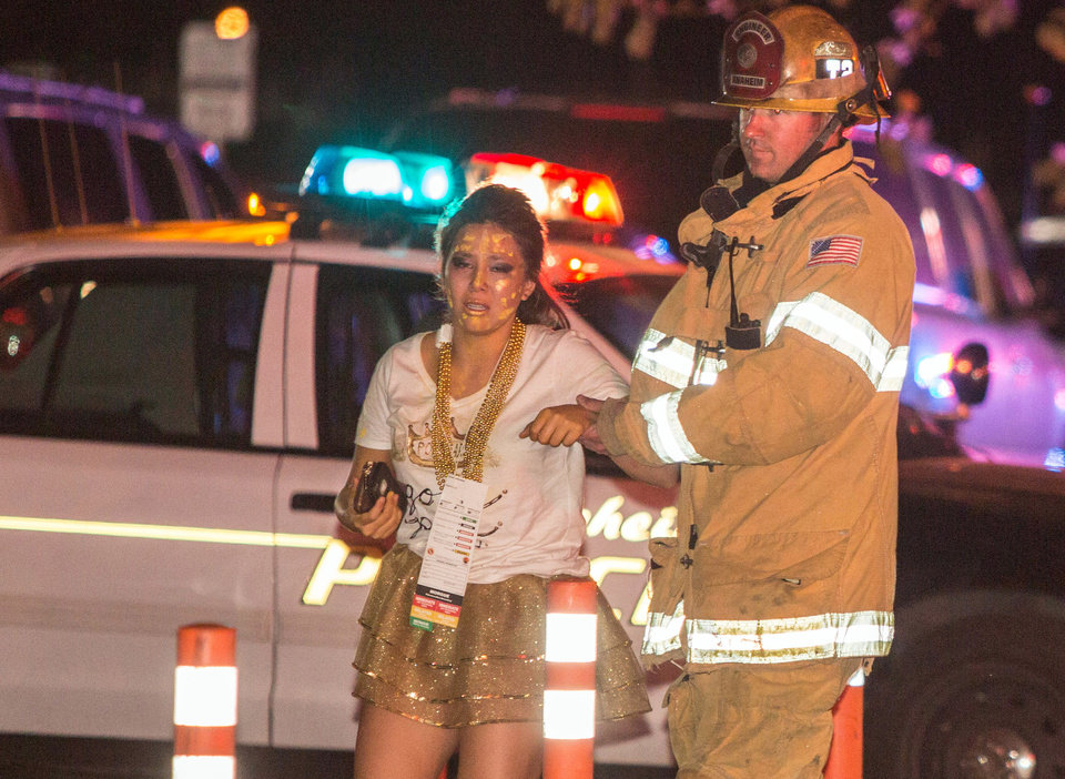 Photo - A firefighter assists an injured student after a stage collapsed during a student event at Servite High School in Anaheim, Calif., Saturday, March 8, 2014. Authorities said 30-40 people were taken to hospitals with mainly minor injuries. (AP Photo/Kevin Warn)