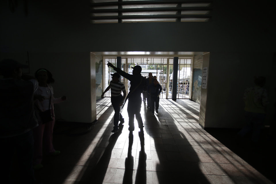 A soldier directs voters inside a polling station during the presidential election in Caracas, Venezuela, Sunday, Oct. 7, 2012. President Hugo Chavez is running against opposition candidate Henrique Capriles. (AP Photo/Fernando Llano)