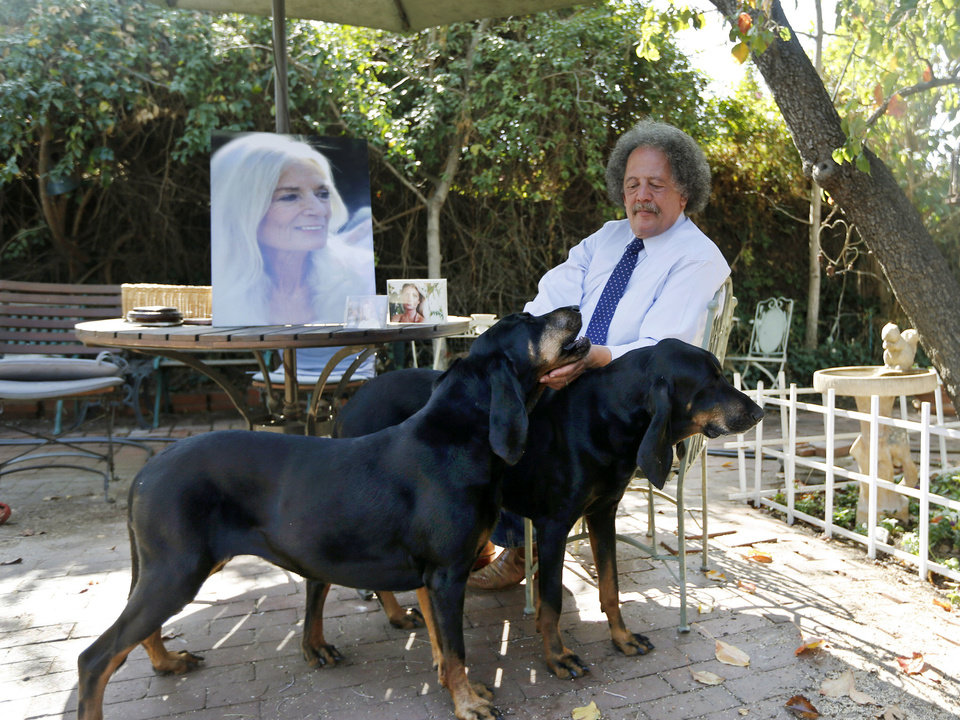 Photo - ADVANCE FOR USE SUNDAY, MAY 11, 2014 AND THEREAFTER - In this Wednesday, Feb. 19, 2014 photo, Jay Westbrook, clinical director of Compassionate Journey, pets his dogs as he sits next to photos of his late wife, Nancy, in their backyard in Los Angeles. There have been thousands of souls he journeyed with to the intersection of living and dying, who helped establish him as one of the foremost experts on hospice care. Then came one death too many - when his beloved Nancy died. (AP Photo/Damian Dovarganes)