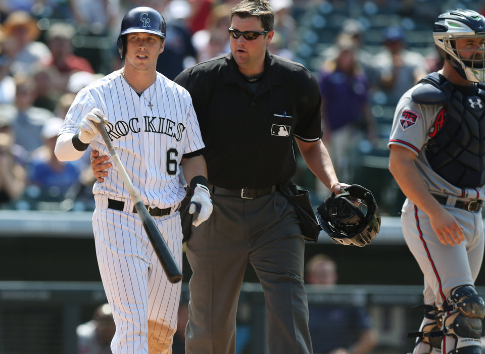 Photo - Colorado Rockies' Corey Dickerson, left, is restrained by home plate umpire Jordan Baker as he walks Dickerson down the first-base line after he was hit by a pitch thrown by Atlanta Braves relief pitcher David Carpenter in the eighth inning of the Rockies' 10-3 victory in a baseball game in Denver on Thursday, June 12, 2014. Braves catcher Evan Gattis, right, looks on. Rockies manager Walt Weiss was ejected for arguing over Dickerson being hit by the pitch. (AP Photo/David Zalubowski)