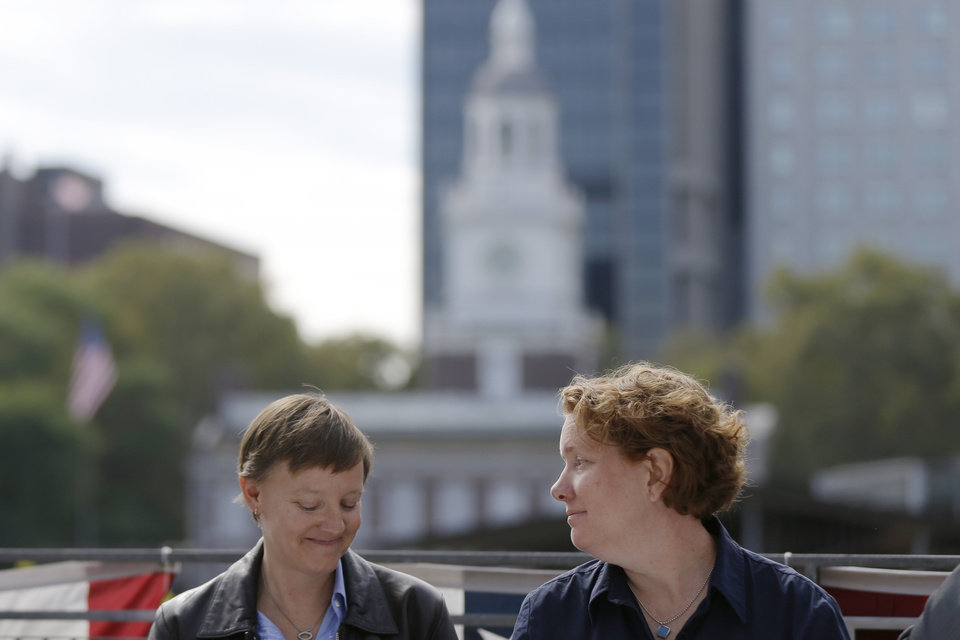 Photo - Cara Palladino right looks at her spouse Isabelle Barker during a news conference, Thursday, Sept. 26, 2013, near Independence Hall in Philadelphia. Cara Palladino and Isabelle Barker, who were legally married in Massachusetts and moved to Pennsylvania, filed a federal lawsuit Thursday aiming to overturn the 1996 amendment to a state law stating same-sex marriages, including those recorded elsewhere, are not legal within the state.(AP Photo/Matt Rourke)