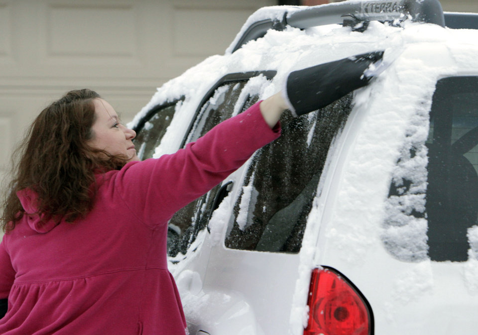 Photo - COLD / WINTER WEATHER: Edmond resident Kim White uses a mitt to clear her car of about an inch of snow that fell overnight in Edmond, OK, Monday, Feb. 13, 2012. By Paul Hellstern, The Oklahoman