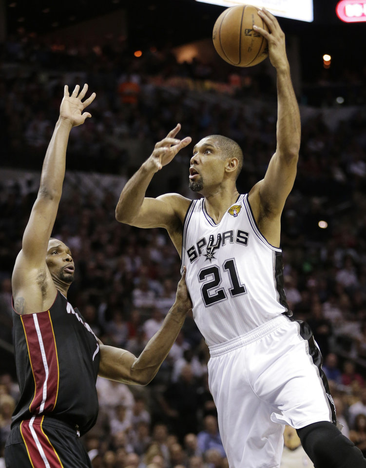 Photo - San Antonio Spurs' Tim Duncan (21) shoots over Miami Heat's Chris Bosh (1) during the first half at Game 4 of the NBA Finals basketball series, Thursday, June 13, 2013, in San Antonio. (AP Photo/Eric Gay)