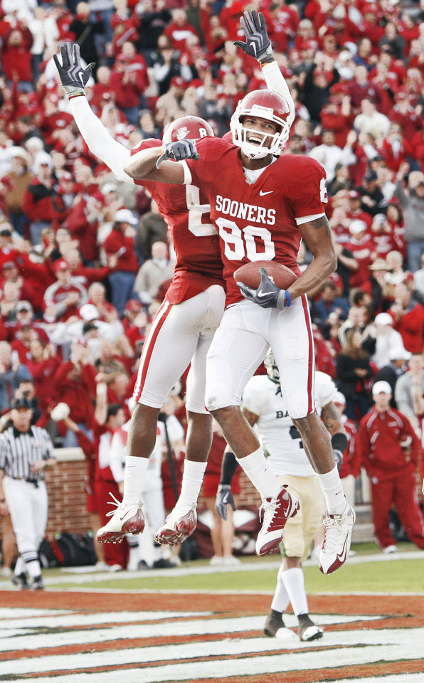 Photo - Adron Tennell, right, celebrates a touchdown with Brandon Caleb against Baylor on Saturday.  Photo by Steve Sisney, The Oklahoman