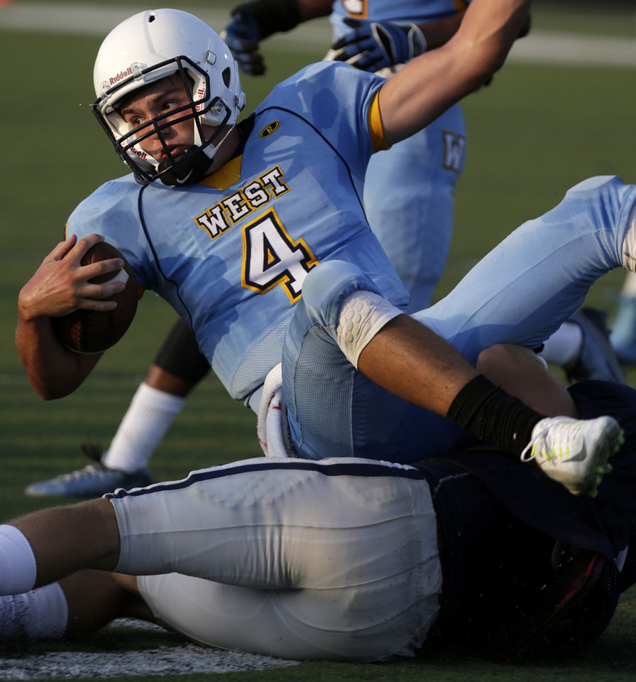 Photo - Putnam City West's Trey Gooch (4) goes down during a scrimmage at Putnam City West High School in Bethany, Thursday, Aug. 21, 2014.  Photo by Garett Fisbeck, For The Oklahoman