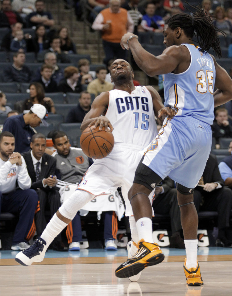 Charlotte Bobcats' Kemba Walker (15) grimaces and keeps the dribble as he gets fouled by Denver Nuggets' Kenneth Faried (35) during the first half of an NBA basketball game in Charlotte, N.C., Saturday, Feb. 23, 2013. (AP Photo/Bob Leverone)