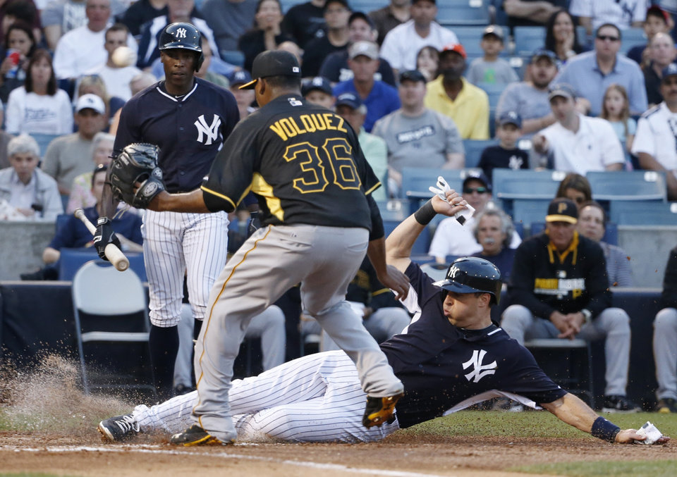 Photo - New York Yankees Mark Teixeira scores on a first-inning wild pitch thrown by Pittsburgh Pirates starting pitcher Edinson Volquez (36) in a spring exhibition baseball game in Tampa, Fla., Friday, March 21, 2014.  The Yankees Alfonso Soriano (12) watches from behind the plate. (AP Photo/Kathy Willens)