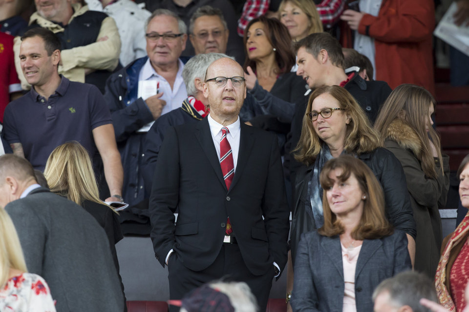 Photo - Manchester United's joint chairman Avram Glazer, center, takes his seat in the stands before the team's English Premier League soccer match against Swansea City at Old Trafford Stadium, Manchester, England, Saturday Aug. 16, 2014. (AP Photo/Jon Super)