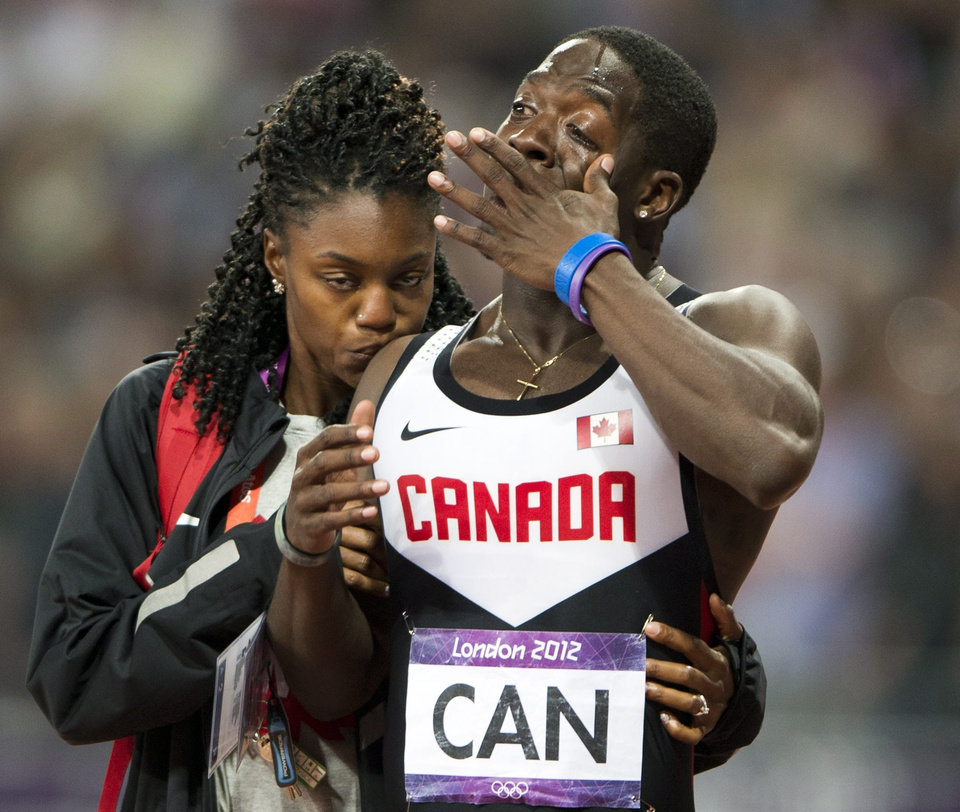Photo -   Canada's Justyn Warner is comforted after the team was disqualified from third place in the men's 4x100-meter relay, for running outside its lane, during Summer Olympics in London, Saturday, Aug. 11, 2012. (AP Photo/The Canadian Press, Ryan Remiorz)
