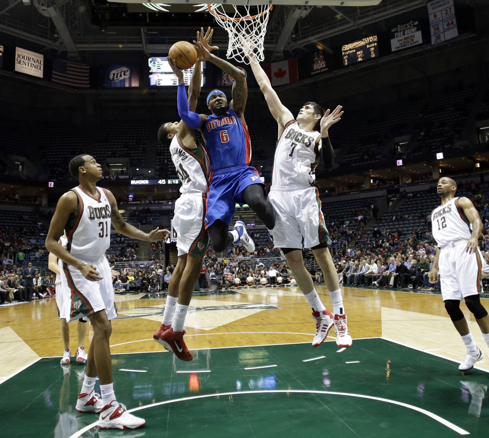 Detroit Pistons' Josh Smith (6) tries to shoot between Milwaukee Bucks' Giannis Antetokounmpo (34) and Ersan Ilyasova (7) during the first half of an NBA basketball game on Wednesday, Dec. 4, 2013, in Milwaukee. (AP Photo/Morry Gash)