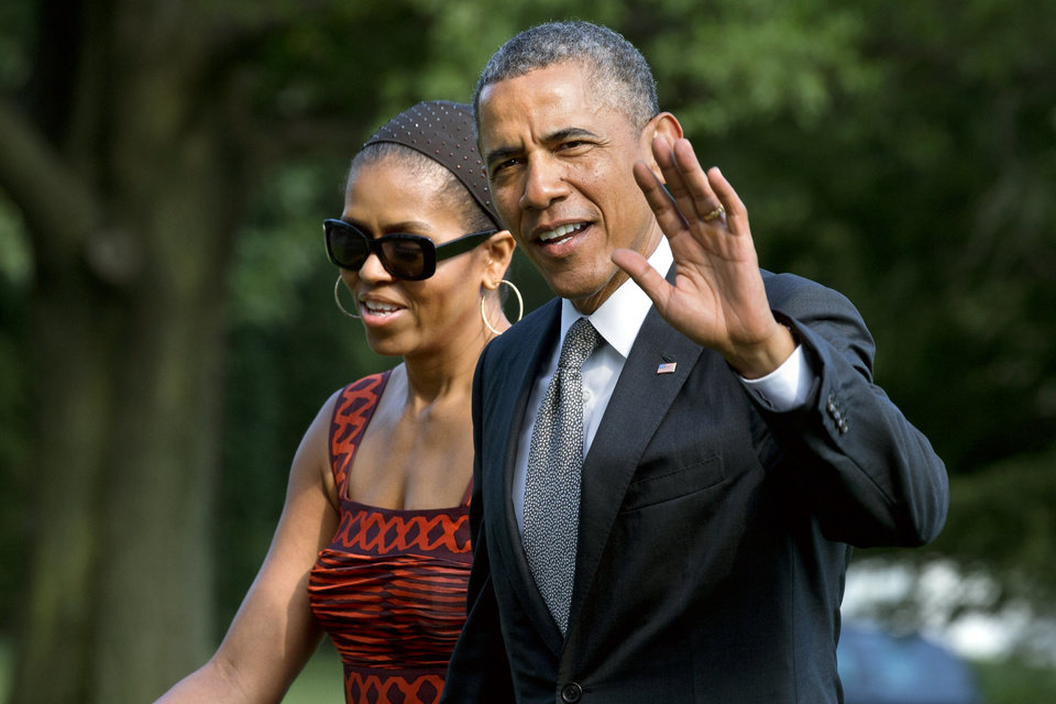 Photo - President Barack Obama waves as he walks with first lady Michelle Obama on their return to the White House from a trip to California, Monday, June 16, 2014, in Washington. (AP Photo/Jacquelyn Martin)