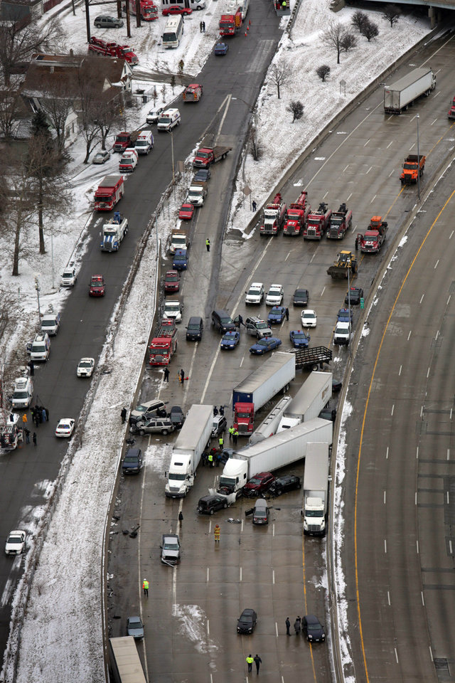 Emergency personnel respond at the scene of one of a mile-long series of crashes along Interstate 75 on the southwest side of Detroit Thursday, Jan. 31, 2013. At least three people are dead, including two children, and 20 more were injured in the pileups. (AP Photo/Detroit Free Press, Romain Blanquart)  DETROIT NEWS OUT;  NO SALES