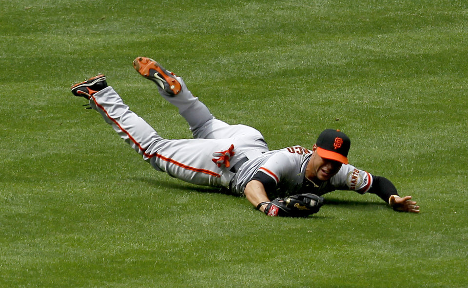 Photo -   San Francisco Giants' Gregor Blanco makes a diving catch on a line drive hit by Arizona Diamondbacks' Ryan Roberts during the fourth inning in an MLB baseball game Sunday, April 8, 2012, in Phoenix.(AP Photo/Ross D. Franklin)