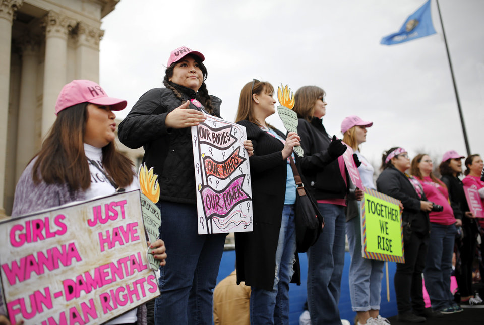 Photo - Women stand on the stage behind one of the guest speakers while she addresses the crowd. A crowd estimated by organizers to be as many as 7,000 people came to the state Capitol in Oklahoma City Saturday, Jan. 21, 2017, to rally, using their voices and signs to express displeasure with the nation's new administration as part of a larger network of marches taking place across the country following Donald Trump's inauguration.   The Women's March on Oklahoma included a walk along Lincoln Blvd., with the Capitol as a backdrop, and a rally on the Capitol's south plaza that featured nearly a dozen speakers.  Photo by Jim Beckel, The Oklahoman