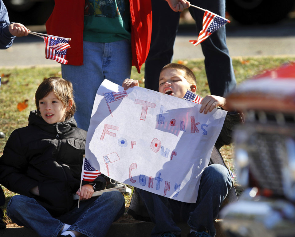 Photo - Students from Soldier Creek Elementary School sit along Douglas Blvd. to watch the parade. A number of students waved flags and held signs of support they made. The city of Midwest City teamed with civic leaders and local merchants to display their appreciation for veterans and active military forces by staging a hour-long Veteran's Day parade that stretched more than a mile and a half along three of the city's busiest streets Monday morning, Nov. 12, 2012. Hundreds of people lined the parade route, many of them waving small American flags that had ben distributed by volunteers who marched near the front of the parade. A fly-over performed by F-16s from the138th Fighter Wing, Oklahoma Air National Guard unit in Tulsa thrilled spectators. Five veterans representing military personnel who served in five wars and military actions served as  Grand Marshals for the parade. Leading the parade was the Naval Reserve seven-story American flag, carried by 100 volunteers from First National Bank of Midwest City, Advantage Bank and the Tinker Federal Credit Union. The flag is 50 feet by 76 feet, weighs 110 pounds and was sponsored by the MWC Chapter of Disabled American Veterans. Photo by Jim Beckel, The Oklahoman
