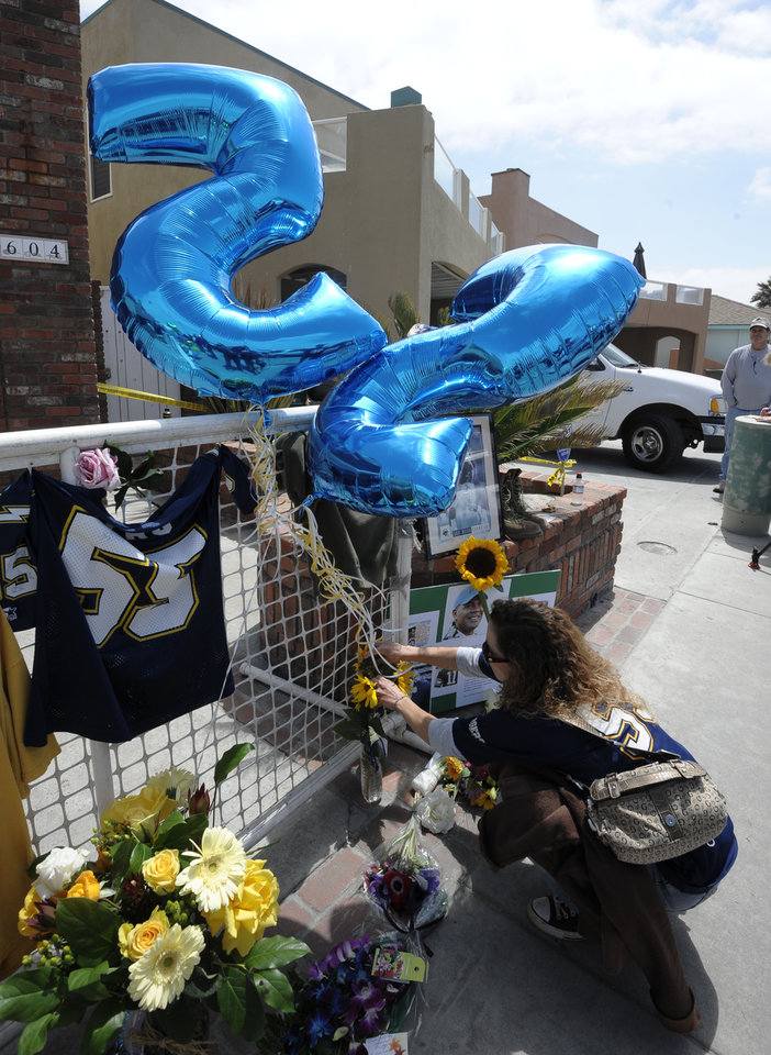 Photo -   San Diego Chargers fan April Court puts flowers next to balloons with Junior Seau's #55 at a memorial in the driveway of the house of former NFL star Junior Seau Thursday, May 3, 2012, in Oceanside, Calif. Seau's death in Oceanside, in northern San Diego County, stunned the region he represented with almost reckless abandon. (AP Photo/Denis Poroy)