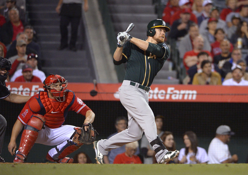 Photo - Oakland Athletics' Brandon Moss watches his three-run home run in front of Los Angeles Angels catcher Chris Iannetta during the fourth inning of a baseball game, Wednesday, April 16, 2014, in Anaheim, Calif. (AP Photo/Mark J. Terrill)