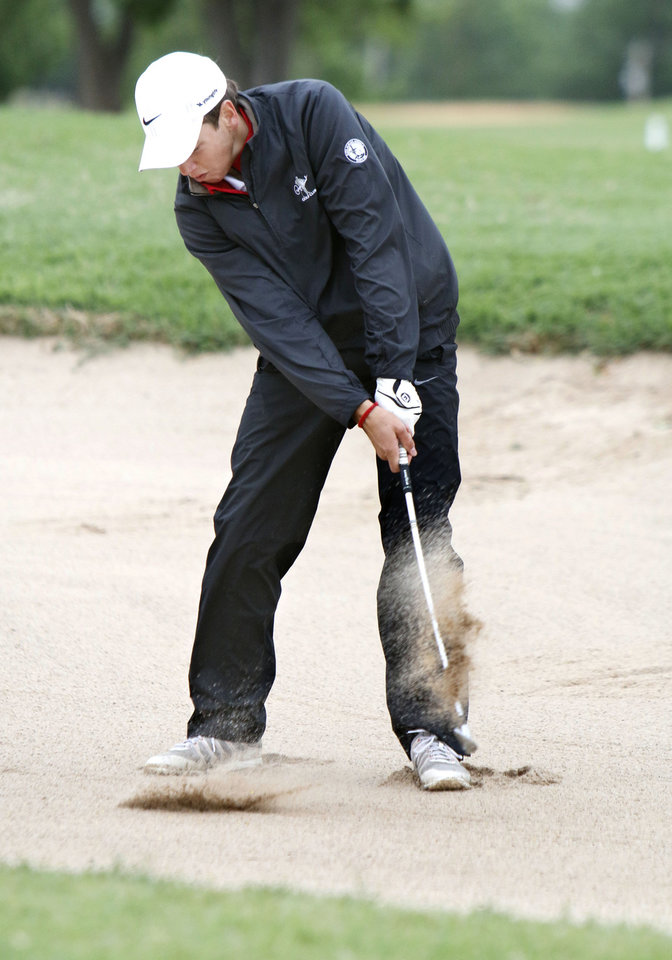 Photo - Metro Christian's Chase Turner chips a shot out of a bunker during the class 4A boy's state golf tournament at the Lake Hefner Golf Course in Oklahoma City, OK, Monday, May 12, 2014,  Photo by Paul Hellstern, The Oklahoman