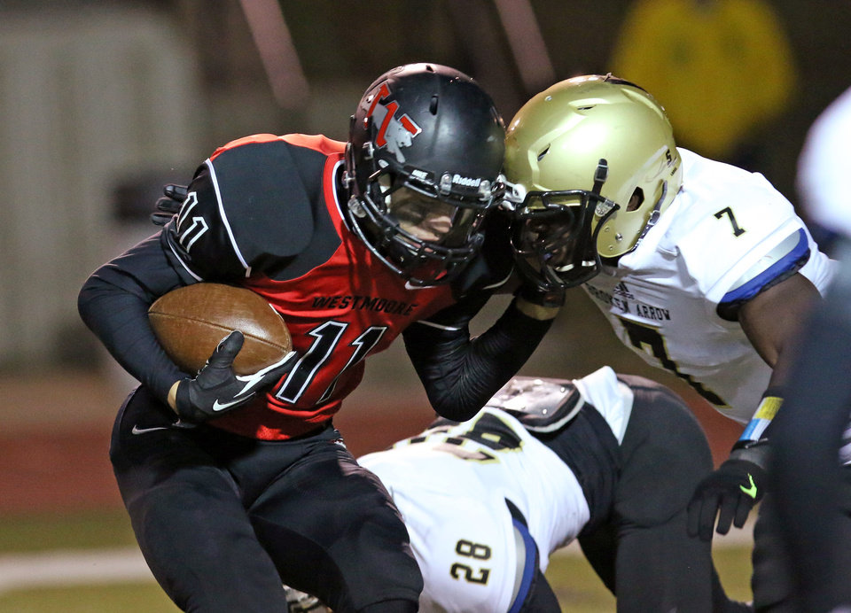 Photo - WM #11 WR Deshawn Lookout fights for more yards as he is hit by BA #7 Gysai Akem after a long catch and run during the high school football game between Broken Arrow and Westmoore at Moore stadium Friday , November 8, 2013. Photo by Doug Hoke, The Oklahoman