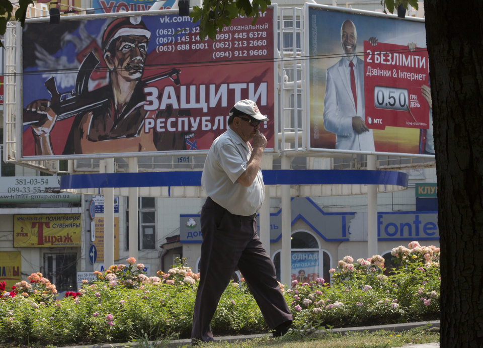 Photo - A man walks past a pro-Russian rebels army's agitation poster, left, in the city of Donetsk, eastern Ukraine, Monday, Aug. 4, 2014. The poster reads 'Protect the Republic!'. (AP Photo/Dmitry Lovetsky)