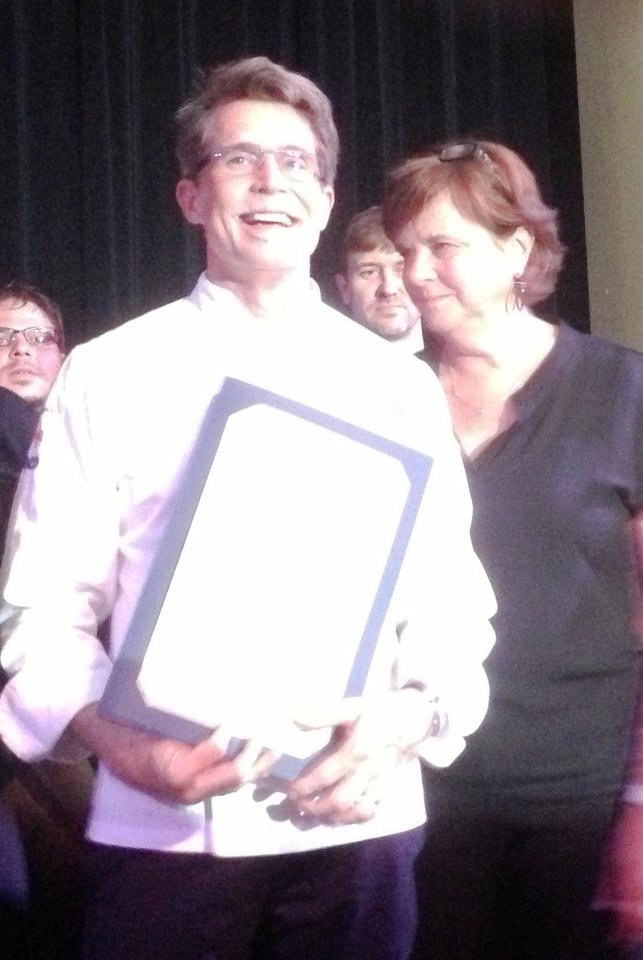 Photo - Rick Bayless poses with his newly receive proclamation from the city of Oklahoma City to make June 24, 2013, Rick Bayless Day.  DAVE CATHEY - THE OKLAHOMAN