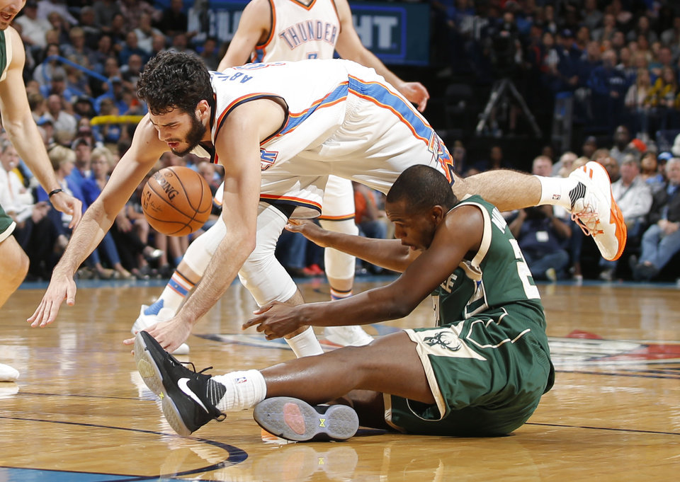 Photo - Oklahoma City's Alex Abrines (8) runs into Milwaukee's Khris Middleton (22) during an NBA basketball game between the Oklahoma City Thunder and the Milwaukee Bucks at Chesapeake Energy Arena in Oklahoma City, Tuesday, April 4, 2017. Alex Abrines left the game after the play. Photo by Bryan Terry, The Oklahoman