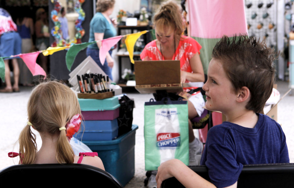 Photo -  Carter Walker and sister Carlee Bea Walker have a caricature drawn by artist Dorinda Hoke, of Kansas City, at the 2013 Paseo Arts Festival. Photo by K.T. King, The Oklahoman Archives   KT King -