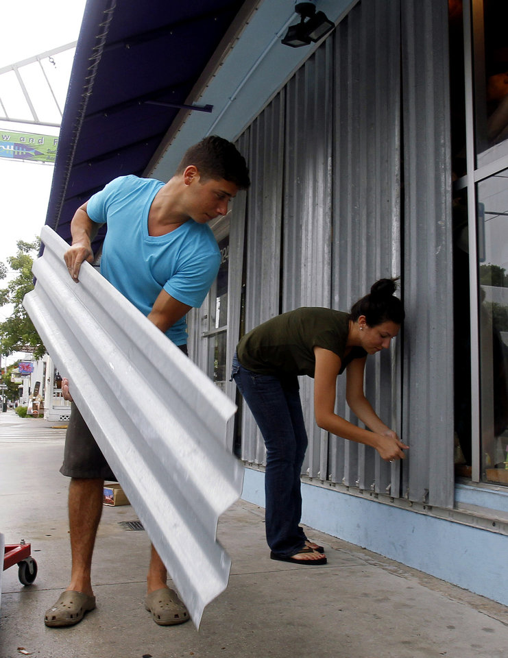 Photo -   Yoni Haim, left, and Jessica Yeshalek board their storefront as they prepare for Tropical Storm Isaac, Saturday, Aug. 25, 2012. Isaac's winds are expected to be felt in the Florida Keys by sunrise Sunday morning. (AP Photo/Alan Diaz)