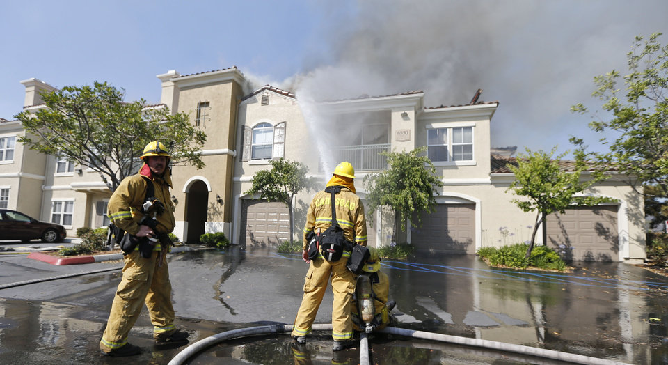 Photo - Firefighters pour water on a condominium complex that was caught in the path of a wildfire Wednesday, May 14, 2014, in Carlsbad, Calif. Flames engulfed suburban homes and shot up along canyon ridges in one of the worst of several blazes that broke out Wednesday in Southern California during a second day of a sweltering heat wave, taxing fire crews who fear the scattered fires mark only the beginning of a long wildfire season. (AP Photo)