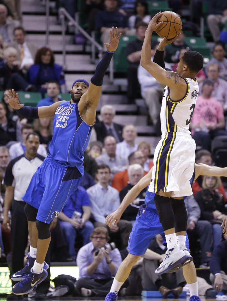 Photo - Utah Jazz's Trey Burke (3) shoots as Dallas Mavericks' Vince Carter (25) defends in the first quarter during an NBA basketball game Wednesday, March 12, 2014, in Salt Lake City. (AP Photo/Rick Bowmer)