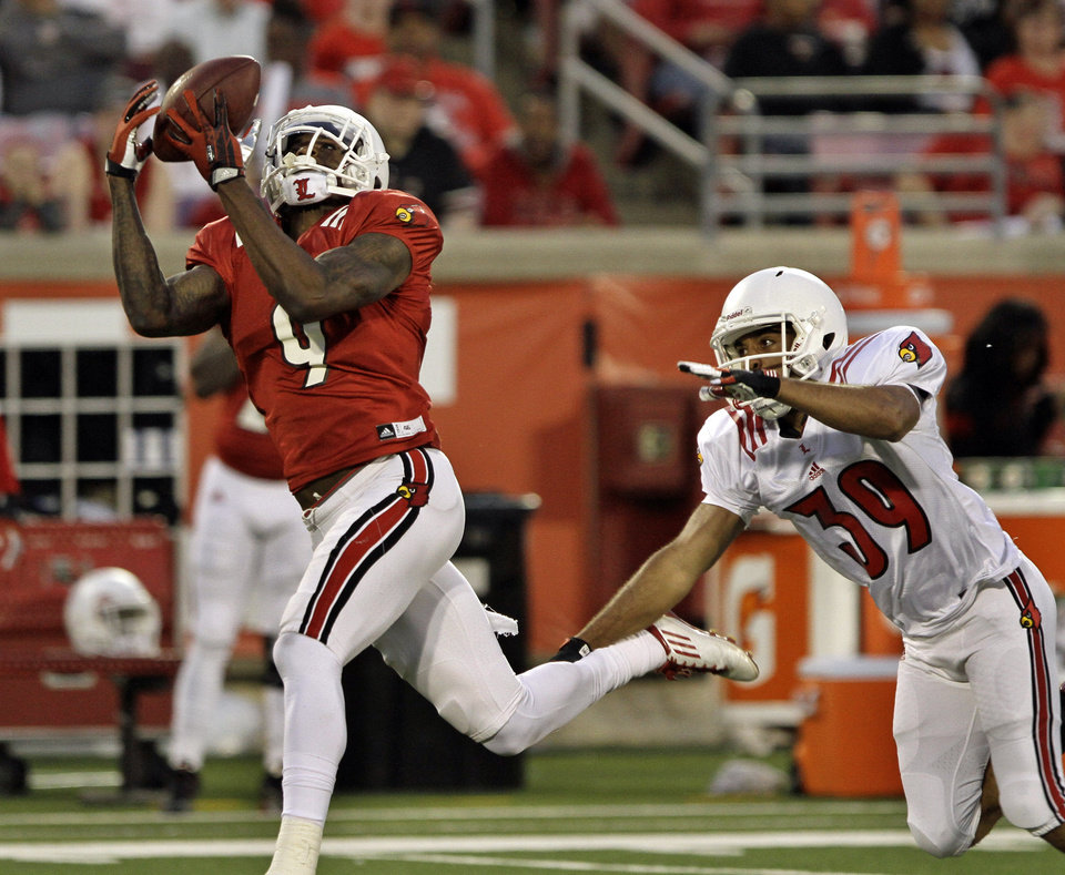 Photo - Louisville's senior wide receiver DeVante Parker (9) makes this catch after getting past defender Jordan Streeter (39) in their NCAA college spring football game in Louisville, Ky., Friday, April 11, 2014.  (AP Photo/Garry Jones)