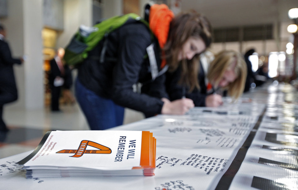 Photo - Oklahoma State sophomores Holly Vetsch and Madison Anders, from left, sign the memory banner during the memorial service for Oklahoma State head basketball coach Kurt Budke and assistant coach Miranda Serna at Gallagher-Iba Arena on Monday, Nov. 21, 2011 in Stillwater, Okla. The two were killed in a plane crash along with former state senator Olin Branstetter and his wife Paula while on a recruiting trip in central Arkansas last Thursday. Photo by Chris Landsberger, The Oklahoman