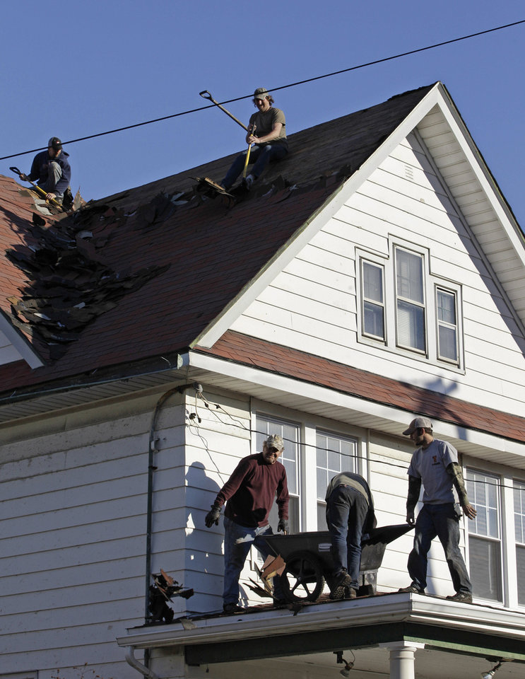 Photo - FILE- In this Dec. 5, 2012 file photo, roofers from Fountain Roofing, a North Atlanta-based company, repair a damaged roof on a home in the storm-damaged Belle Harbor section of the Queens borough of New York. Although City officials are poised to proclaim success in reaching their Build it Back program's first milestone of 500 projects started and 500 reimbursement checks sent by Labor Day, an estimated 15,000 homes are still waiting for fixing or reimbursement checks. (AP Photo/Kathy Willens, File)