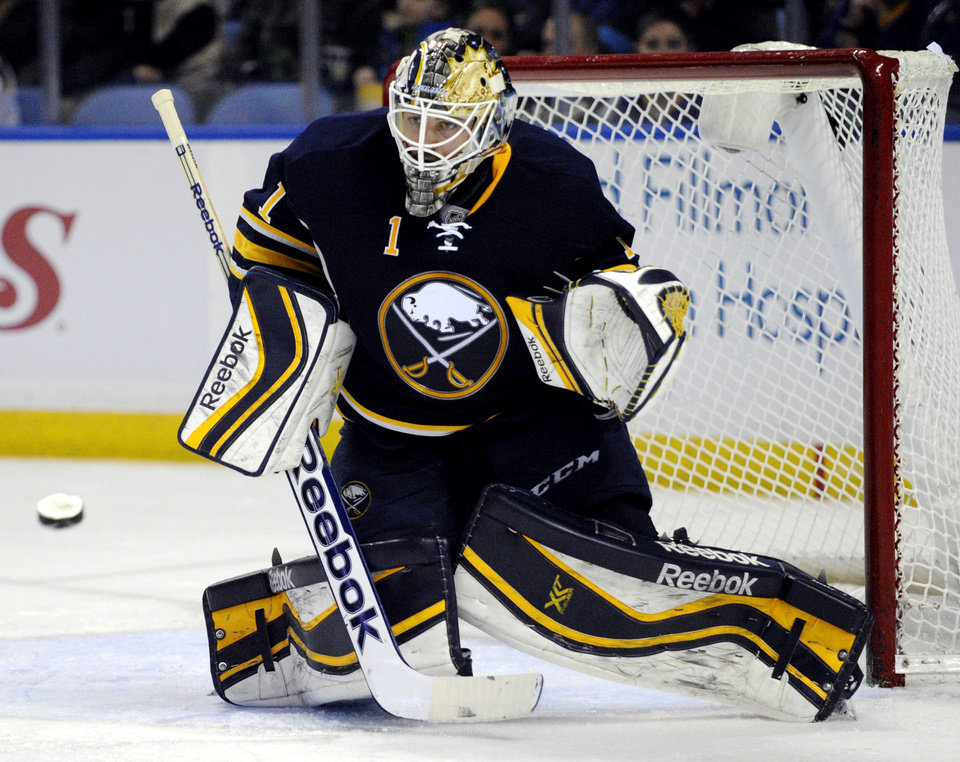 Photo - Buffalo Sabres goaltender Jhonas Enroth, of Sweden, watches an incoming shot during the second period of an NHL hockey game against the Nashville Predators in Buffalo, N.Y., Tuesday, March 11, 2014. (AP Photo/Gary Wiepert)