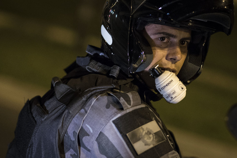 Photo - A riot police officer uses his front teeth to hold onto to a non-lethal grenade during an anti-government protest near the Cidade de Deus, or City of God slum, in Rio de Janeiro, Brazil, Friday, June 21, 2013. City centers around Brazil were still smoldering on Friday after 1 million protesters took to the streets amid growing calls on social media for a general strike next week. While most protesters were peaceful, some small groups clashed violently with police, who responded in some cases with tear gas, pepper spray and rubber bullets. (AP Photo/Felipe Dana)