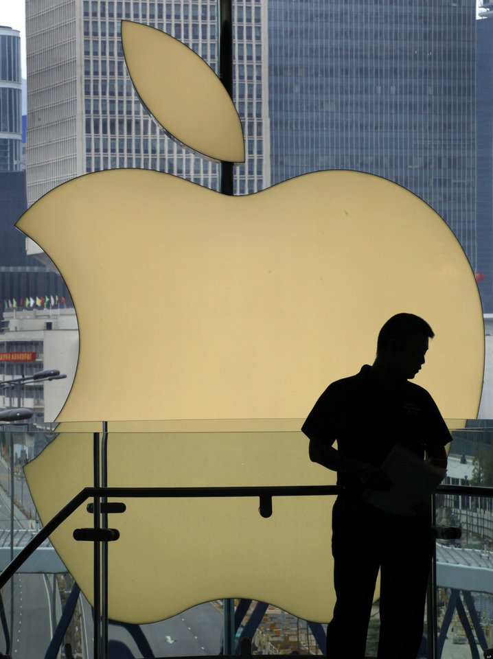A customer stands near an Apple logo before its lighting is turned off to mourn the Apple founder and former CEO Steve Jobs at an Apple store in Hong Kong, Thursday, Oct. 6, 2011. Jobs died on Wednesday at the age of 56. (AP Photo/Vincent Yu)