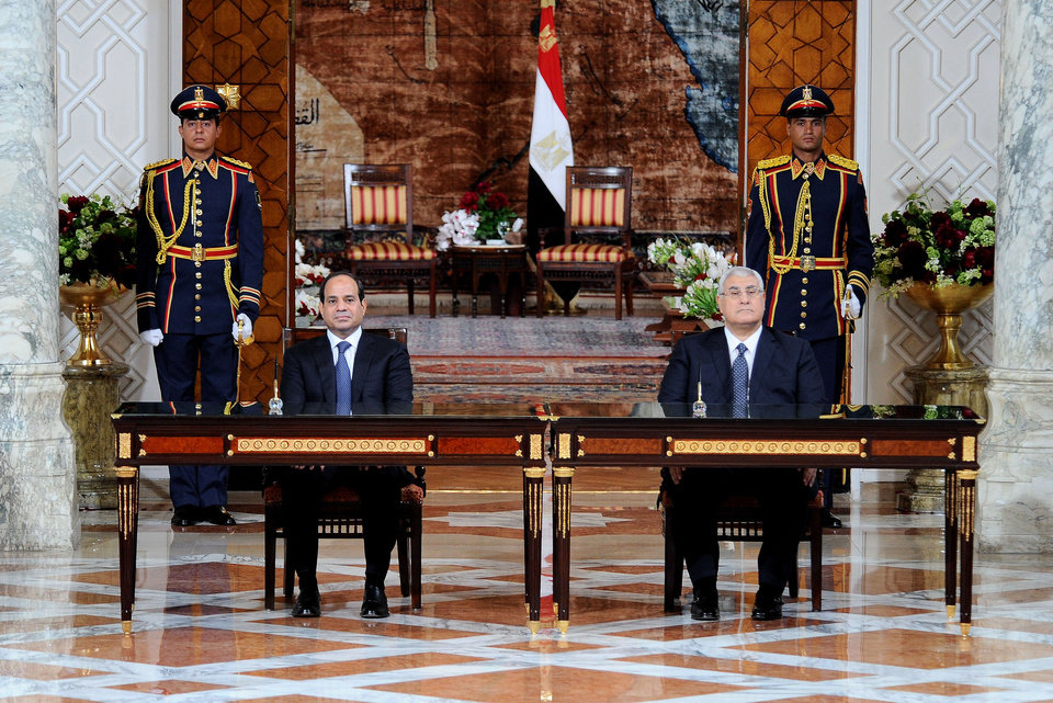 Photo - In this image released by Egypt's state news agency MENA, President Abdel-Fattah el-Sissi, left, and outgoing interim President Adly Mansour attend El-Sissi's inaugural ceremony at the Presidential Palace in Cairo, Egypt, Sunday, June 8, 2014. Egypt's newly sworn-in president called on his country Sunday to build a more stable future after years of turmoil and revolt, asking them to work hard so that their rights and freedoms could grow. Retired Field Marshal El-Sissi, the former military chief who ousted Egypt's first freely elected leader last July, addressed a ceremony held at a presidential palace in Cairo hours after he was sworn in by the Supreme Constitutional Court. (AP Photo/MENA)