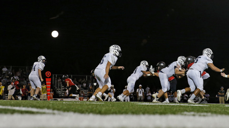 Photo - A full moon rises during a high school football game between Crossings Christian and Minco in Oklahoma City, Friday, Sept. 13, 2019. [Bryan Terry/The Oklahoman]
