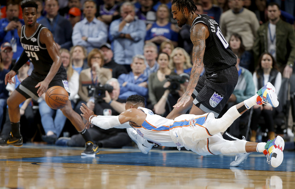 Photo - Oklahoma City's Russell Westbrook (0) falls down as Sacramento's Buddy Hield (24) and Willie Cauley-Stein (00) watch during an NBA basketball game between the Oklahoma City Thunder and the Sacramento Kings at Chesapeake Energy Arena in Oklahoma City, Saturday, Feb. 23, 2019. Sacramento won 119-116. Photo by Bryan Terry, The Oklahoman