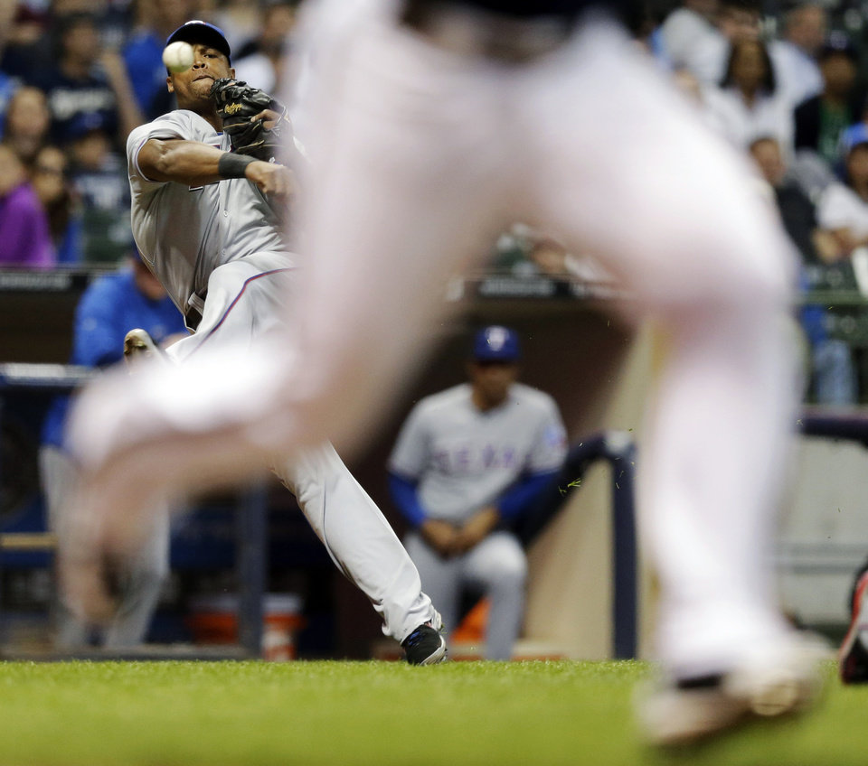 Photo - Texas Rangers third baseman Adrian Beltre makes a wild throw on a bunt by Milwaukee Brewers' Carlos Gomez during the fourth inning of a baseball game Wednesday, May 8, 2013, in Milwaukee. (AP Photo/Morry Gash)