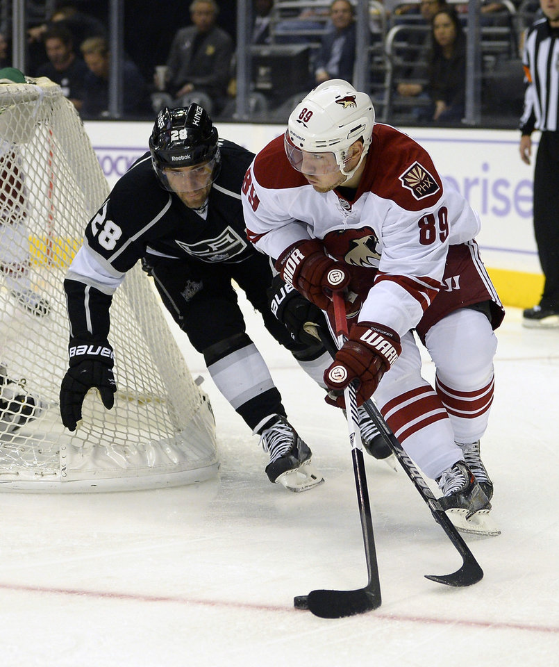 Photo - Los Angeles Kings center Jarret Stoll, left, and Phoenix Coyotes right wing Mikkel Boedker, of Denmark, battle for the puck during the first period of their NHL hockey game on Thursday, Oct. 24, 2013, in Los Angeles. (AP Photo/Mark J. Terrill)