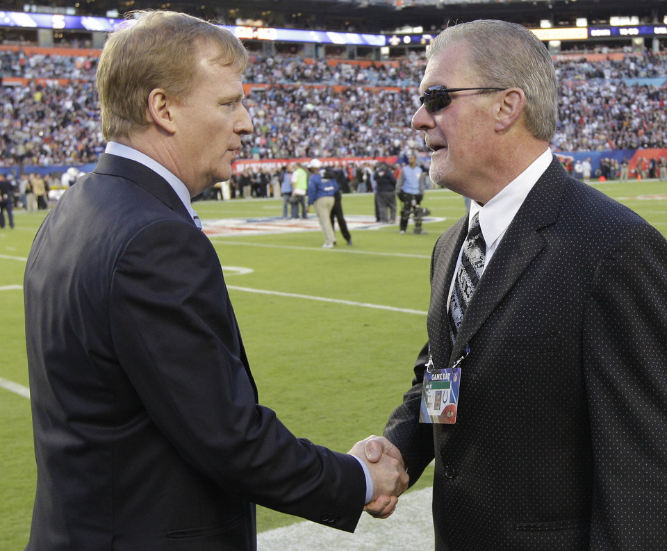 Photo - FILE - In this Feb. 7, 2010, file photo, NFL Commissioner Roger Goodell, left, shakes hands with Indianapolis Colts owner Jim Irsay before the start of the NFL Super Bowl XLIV football game between the Colts and New Orleans Saints in Miami. The NFL suspends Irsay for six games and fines him a maximum $500,000 after he pleads guility to a misdemeanor in a drug case stemming from a March traffic stop. Commissioner Goodell says owners must be held to a higher standard than players. (AP Photo/David J. Phillip, File)
