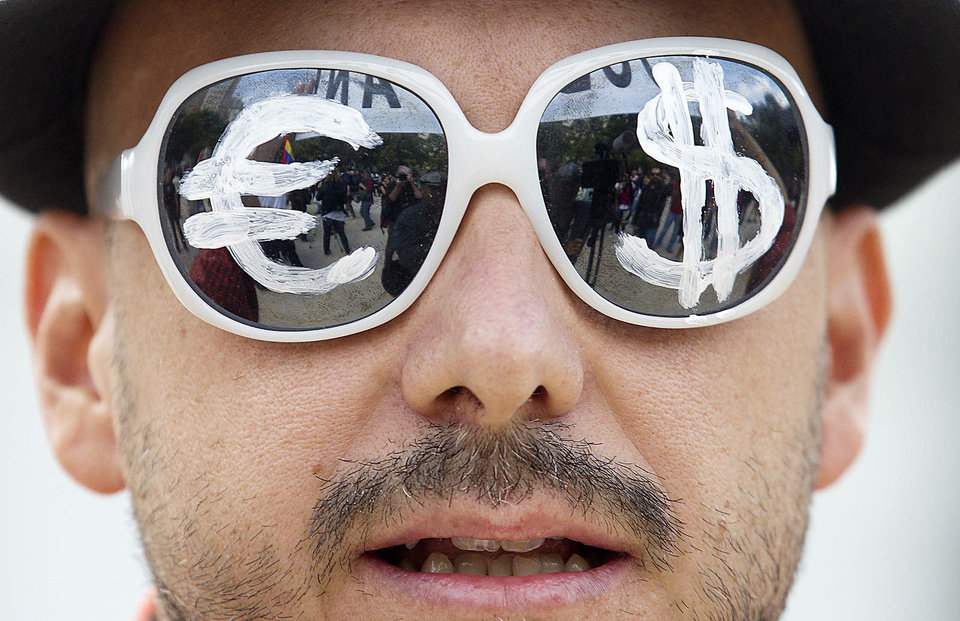 A man wears glasses with the euro and dollar symbols painted on the lenses Sept. 25 before protesting the conservative government's handling of the economic crisis and to demand fresh elections in Madrid. AP Archives Photo
