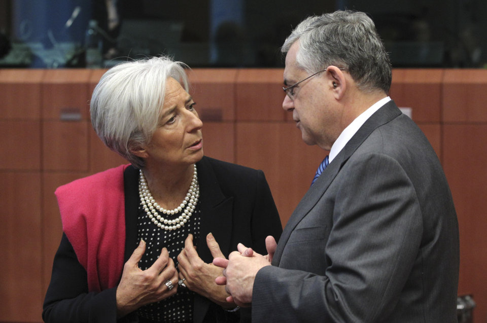 Photo -   Managing Director of the International Monetary Fund Christine Lagarde, left, speaks with Greek Prime Minister Lucas Papademos during a round table meeting of eurozone finance ministers at the EU Council building in Brussels on Monday, Feb. 20, 2012. Eurozone governments will likely approve on Monday a long-elusive rescue package for Greece, saving it from a potentially calamitous bankruptcy next month, senior officials said. But finance ministers meeting in Brussels will have a few last issues to wrangle over, such as tighter controls over Greece's spending and further cuts to the country's debt load. (AP Photo/Yves Logghe)