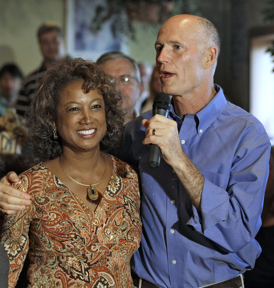 FILE- In this Oct. 26, 2010 file photo, Florida Republican gubernatorial candidate Rick Scott, right, puts his arm around running mate Rep. Jennifer Carroll, R-Jacksonville, during a campaign stop in New Port Richey, Fla. Carroll abruptly resigned Wednesday, March 13, 2012 after authorities questioned her ties into internet cafes that authorities say are fronts for gambling. (AP Photo/Chris O'Meara, File)